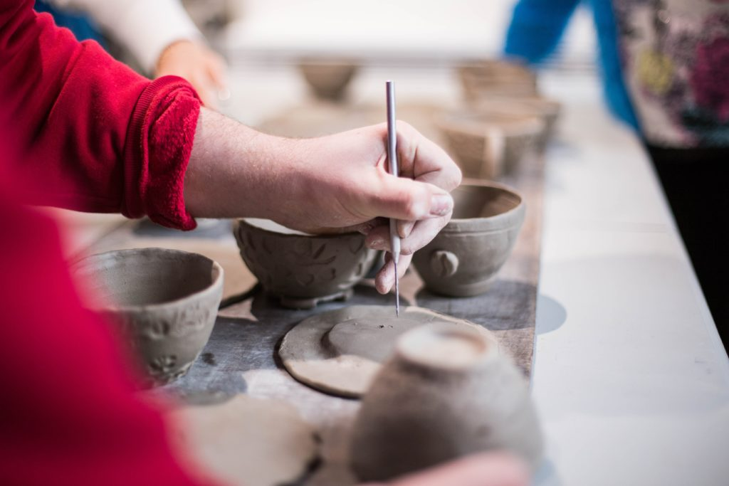 person doing clay containers